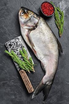 Carpa argentata di pesce intero crudo. sfondo nero. vista dall'alto.