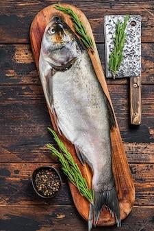 Pesce intero crudo carpa d'argento su un tagliere con rosmarino.