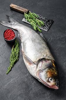 Carpa argentata di pesce intero crudo con pepe rosa e rosmarino