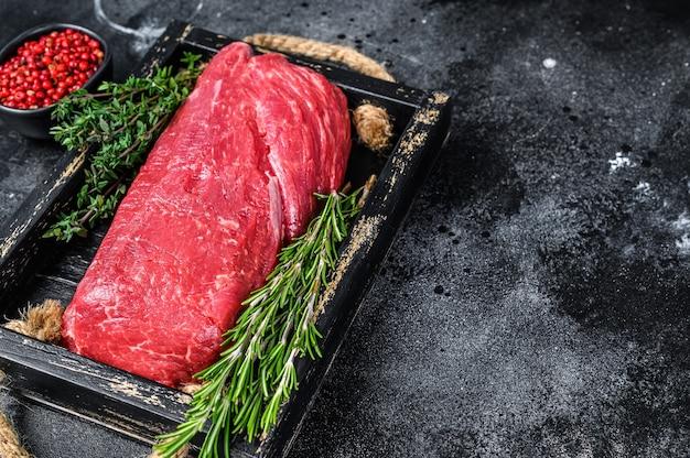 Carne di manzo filetto intero crudo su un vassoio di legno con erbe aromatiche