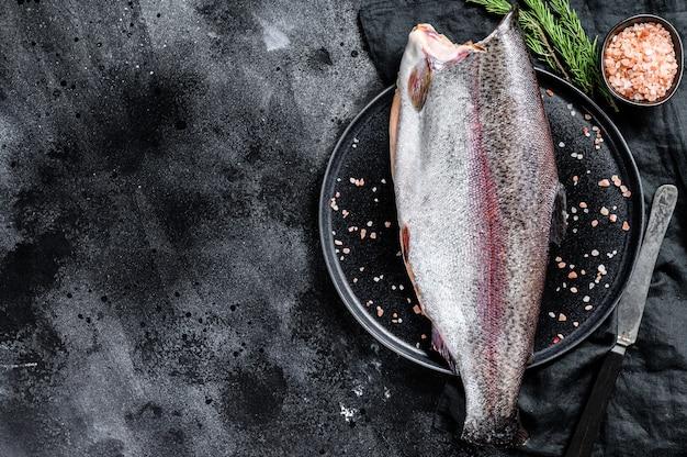 Pesce trota crudo intero senza testa, con sale e rosmarino. .