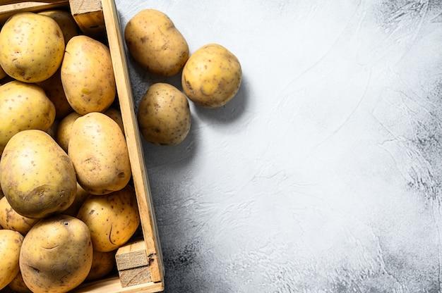 Patate organiche gialle crude in una scatola di legno. sfondo grigio. vista dall'alto. copia spazio.