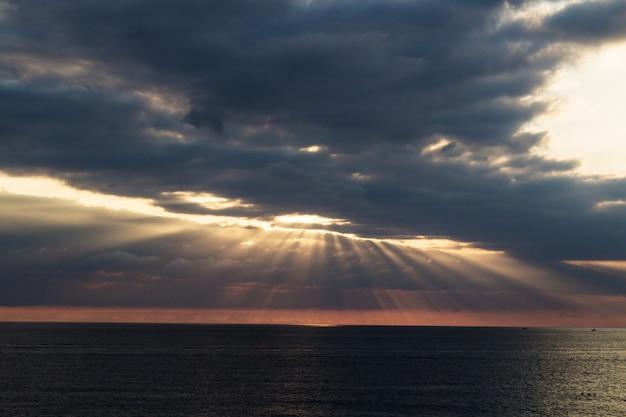 Il raggio del sole si fa strada attraverso le nuvole nel mare. scena drammatica