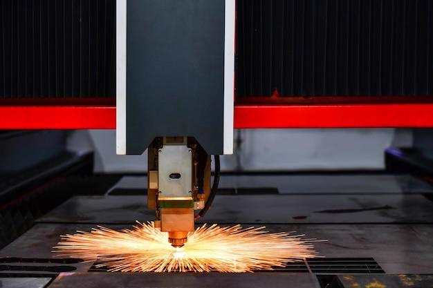 Raytools macchina con testa tagliata al laser durante il taglio della lamiera con la luce scintillante in fabbrica