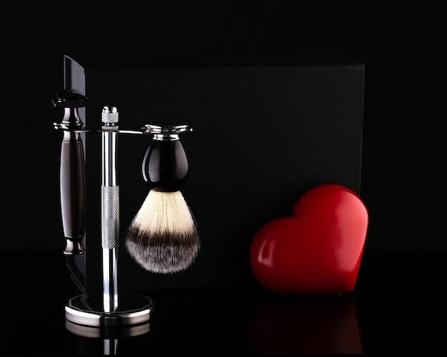 Rasoio e pennello su supporto e scatola nera, cuore rosso su fondo nero