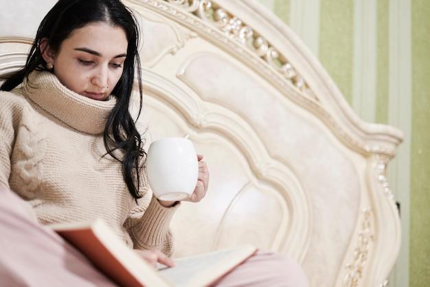Leggere a letto giovane donna che beve caffè e legge un libro a letto la femmina multirazziale legge un libro