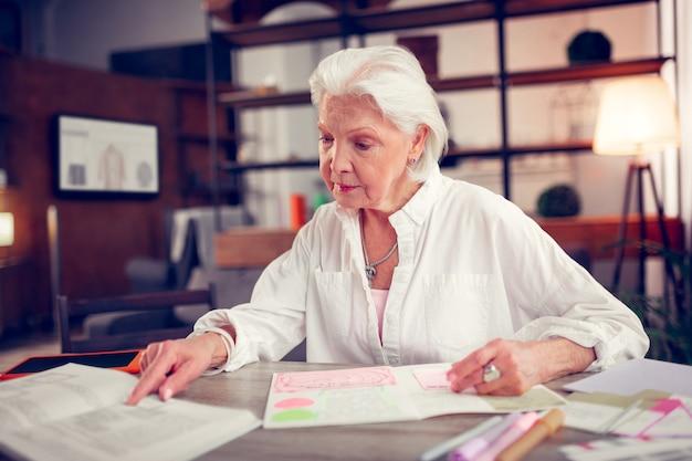 Leggere il libro. bella donna dai capelli grigi che indossa una camicetta bianca leggendo il libro che ha tempo libero
