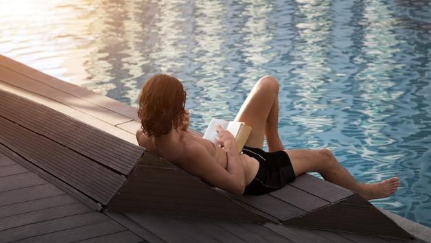 Leggere un libro vicino al bordo piscina e prendere il sole per rilassarsi in estate