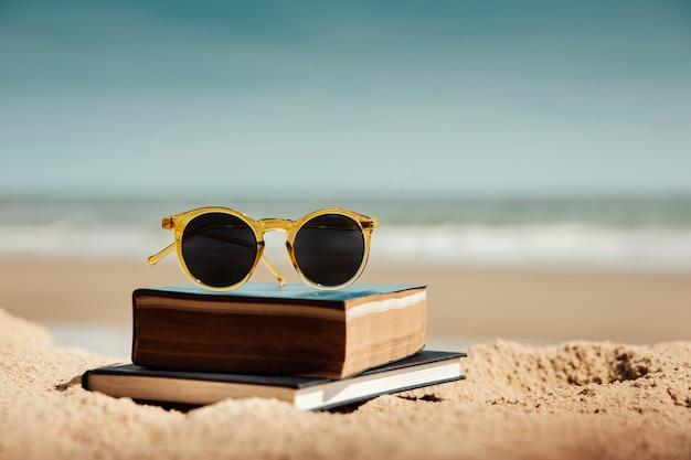 Libro di lettura all'aperto nel concetto di estate. libro e occhiali da sole sulla sabbia della spiaggia in una giornata di sole