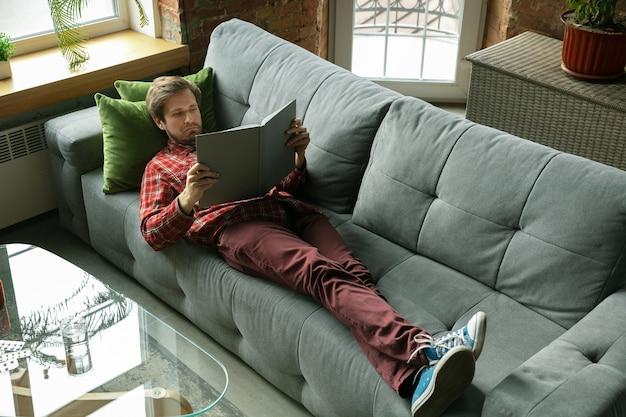 Libro di lettura sul divano. uomo caucasico che resta a casa durante la quarantena a causa del coronavirus, diffusione del covid-19