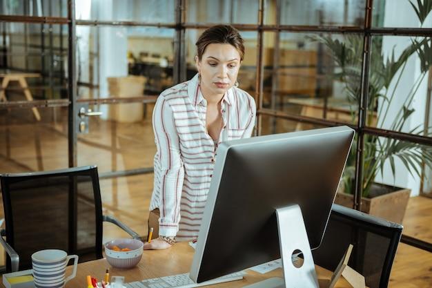 Lettura lettera commerciale. interior designer dai capelli scuri che legge una lettera commerciale dal suo cliente costante
