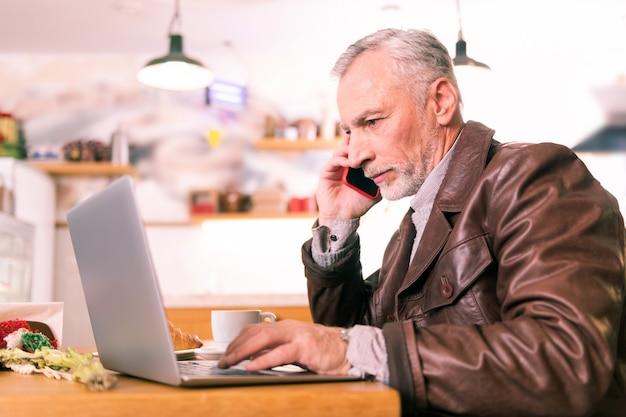 Lettura di documenti. uomo d'affari maturo occupato che chiama il suo socio in affari dopo aver letto i documenti