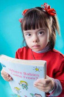 Leggere il libro educativo. bella giovane donna con grandi occhi marroni che trasportano un libro spesso su argomento controverso
