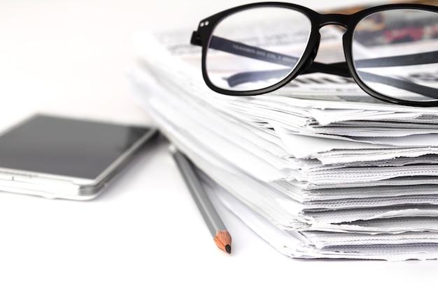 Leggendo gli occhiali con l'accatastamento di sfondo del giornale