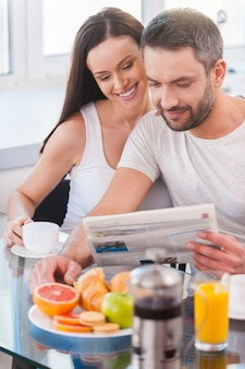 Leggere insieme il giornale fresco. bella giovane coppia che si lega e legge il giornale insieme mentre è seduta in cucina e fa colazione