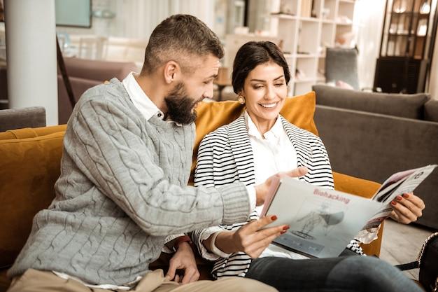 Lettura del catalogo dei mobili. coppia brillante positiva che decide sull'attrezzatura dei futuri appartamenti mentre riposa sui mobili del negozio