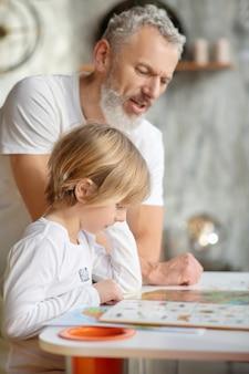 Leggere insieme. un ragazzo che legge un libro colorato insieme a suo nonno