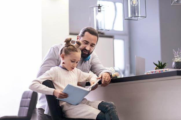 Leggere insieme. ragazza carina dai capelli lunghi dagli occhi azzurri che indossa orecchini luminosi leggendo un libro insieme a suo padre