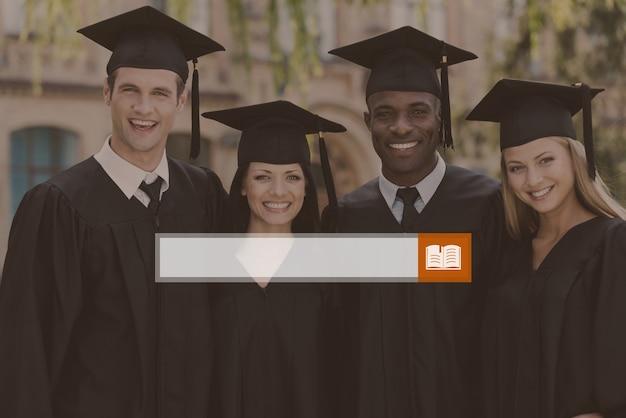 Pronto per un futuro luminoso. quattro laureati in abiti da laurea in piedi l'uno vicino all'altro e sorridenti