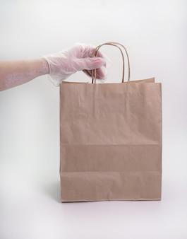 Consegna pronta concetto, una mano guantata di una donna che tiene un sacco di carta su un muro bianco isolato