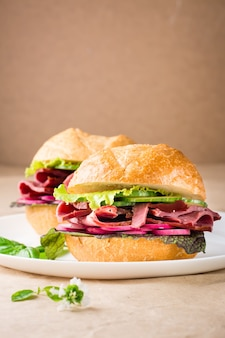 Hamburger pronto con pastrami, verdure e basilico su un piatto su carta artigianale. fast food americano.. copia spazio