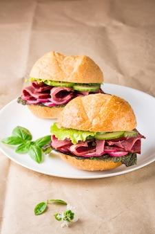 Hamburger pronti con pastrami, verdure e basilico su un piatto su carta artigianale. fast food americano.