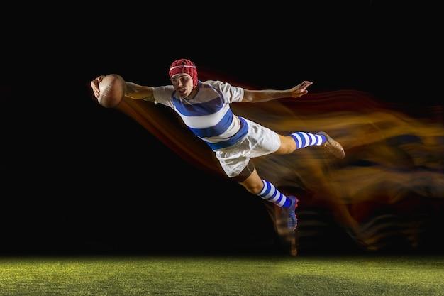 Pronto a volare per vincere. un uomo caucasico che gioca a rugby allo stadio in condizioni di luce mista. montare il giovane giocatore maschio in movimento o in azione durante il gioco sportivo. concetto di movimento, sport, stile di vita sano.
