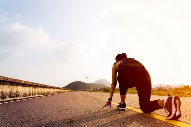Pronti via. donna in esecuzione in posizione di partenza e andando a correre su una lunga strada