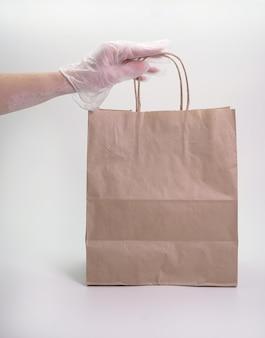 Concetto pronto di consegna dell'alimento, la mano guantata di una donna tiene un sacco di carta con alimento su un fondo bianco isolato