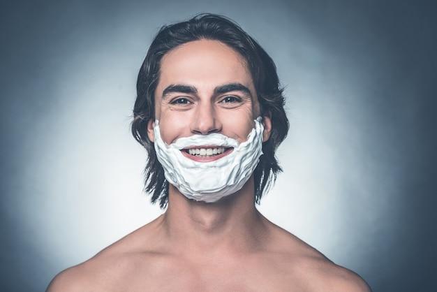 Pronto per la rasatura mattutina. ritratto di giovane uomo a torso nudo con crema da barba sul viso che guarda l'obbiettivo e sorride mentre sta in piedi su sfondo grigio