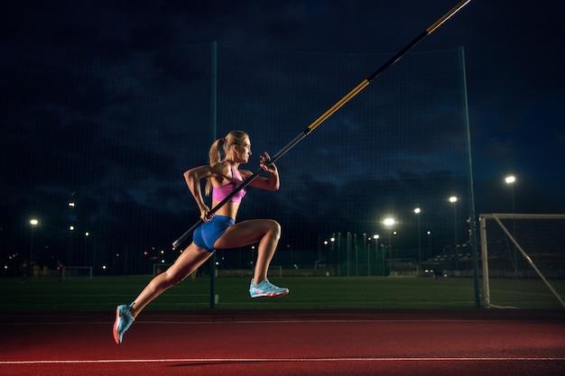 Pronto a superare le difficoltà. formazione professionale femminile di salto con l'asta allo stadio la sera. praticare all'aperto. concetto di sport