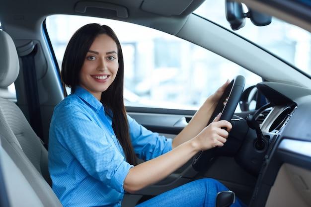 Pronto per la strada. bella giovane donna che sorride felicemente alla macchina fotografica mentre sedendosi in una nuova automobile al salone dell'automobile