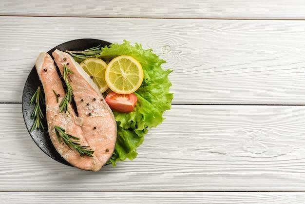 Bistecca di color salmone pronta con lattuga, limone e pomodoro su una parete di tavolo in legno con spazio di copia.