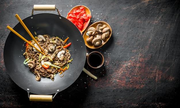 Tagliatelle di soba pronte con zenzero, funghi e salsa di soia. su fondo rustico scuro