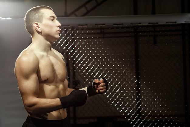 Pronto per un po 'di dolore? ritratto a mezzo busto di un giovane combattente maschio in forma in una gabbia di combattimento