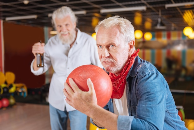 Pronto a colpire. uomo invecchiato piacevole che tiene una palla da bowling mentre si prepara a colpire uno sciopero