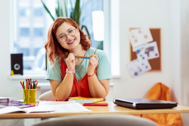 Pronto a studiare. gioiosa bella donna che sorride mentre è seduta alla scrivania