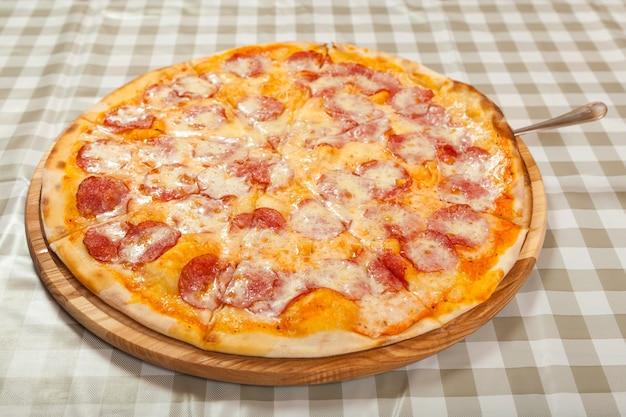 Pizza deliziosa sottile pronta sul tavolo in un caffè