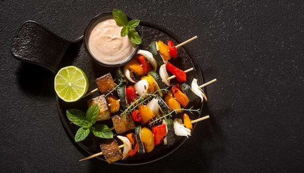 Spiedini vegani pronti di verdure e tofu affumicato con salsa di anacardi e paprika affumicata su fondo nero