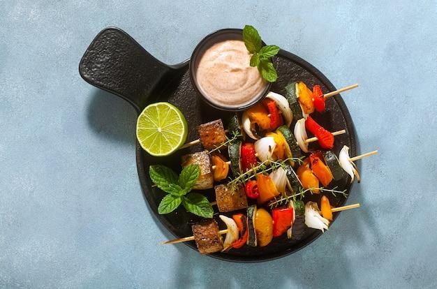 Spiedini vegani pronti di verdure e tofu affumicato con salsa di anacardi e paprika affumicata su fondo blu