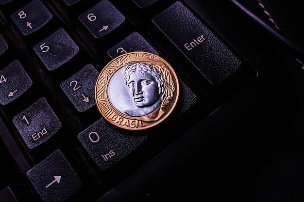 Una vera moneta da 1 sulla tastiera di un computer Foto Premium