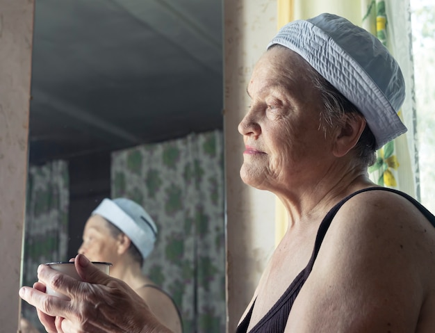Ritratto di una vera donna invecchiata, contadina sorridente stanca dopo il lavoro che riposa a casa con una tazza e guarda