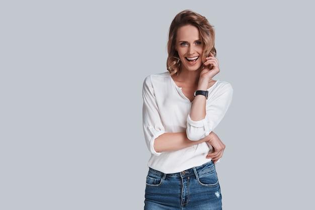 Vera bellezza. attraente giovane donna in abbigliamento casual che guarda la macchina fotografica e sorride mentre si trova in piedi su uno sfondo grigio