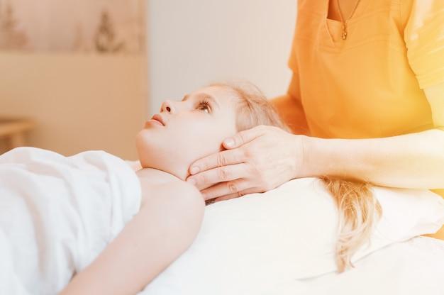 Le mani di un vero dottore osteopata fanno terapia fisiologica ed emotiva per una bambina di otto anni. sessione di trattamento di osteopatia pediatrica. medicina alternativa. prendersi cura della salute del bambino. bagliore