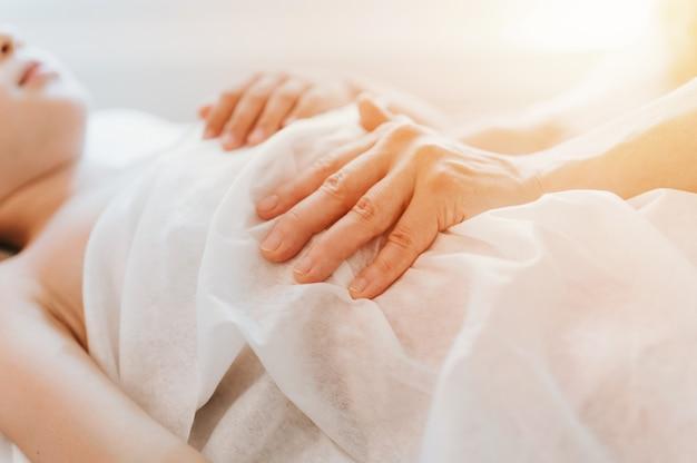 Le mani di un vero medico osteopata fanno terapia fisiologica ed emotiva per una bambina di otto anni. sessione di trattamento di osteopatia pediatrica. medicina alternativa. prendersi cura della salute del bambino. bagliore