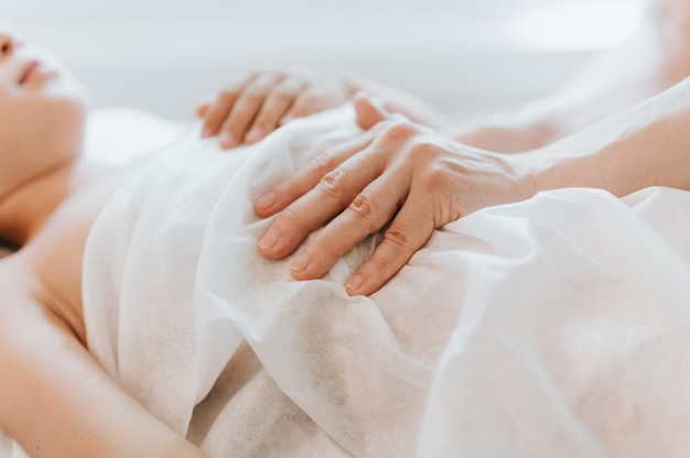 Le mani di un vero medico osteopata fanno terapia fisiologica ed emotiva per una bambina di otto anni. sessione di trattamento di osteopatia pediatrica. medicina alternativa. prendersi cura della salute del bambino