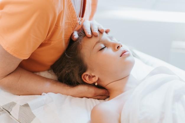 Le mani di un vero dottore osteopata fanno terapia fisiologica ed emotiva per una bambina di otto anni. sessione di trattamento di osteopatia pediatrica. medicina alternativa. prendersi cura della salute del bambino
