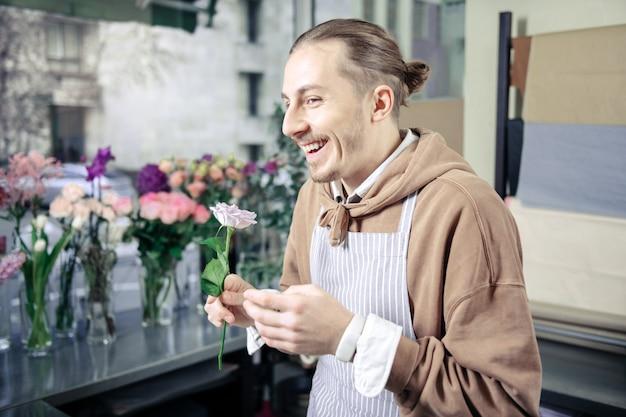 Vere emozioni. fiorista allegro mantenendo il sorriso sul suo volto mentre si gode il suo lavoro