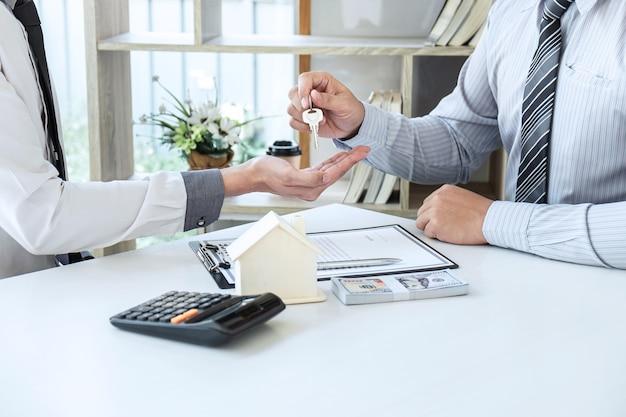 L'agente immobiliare presenta un mutuo per la casa e invia le chiavi al cliente dopo aver firmato il contratto