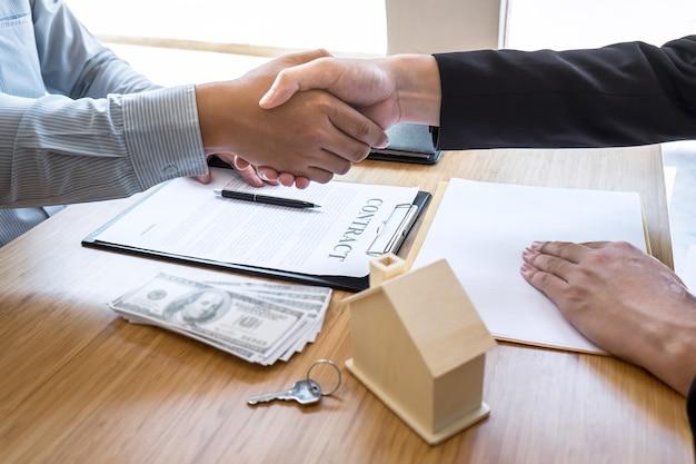 L'agente immobiliare sta stringendo la mano dopo un buon affare e sta dando le chiavi di casa al cliente
